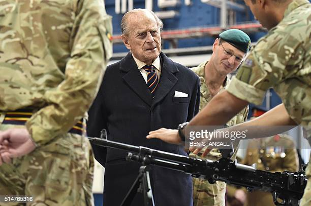 Prince Philip Duke of Edinburgh ColonelinChief Royal Electrical and Mechanical Engineers speaks to a soldier who is demonstrating the operation of a...