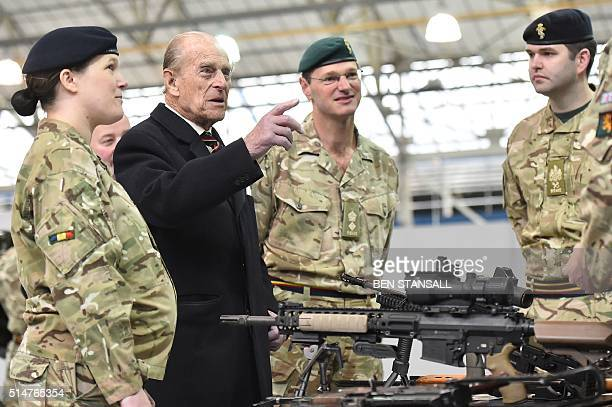 Prince Philip Duke of Edinburgh ColonelinChief Royal Electrical and Mechanical Engineers speaks to soldiers in a hangar with weapons on a desk in...