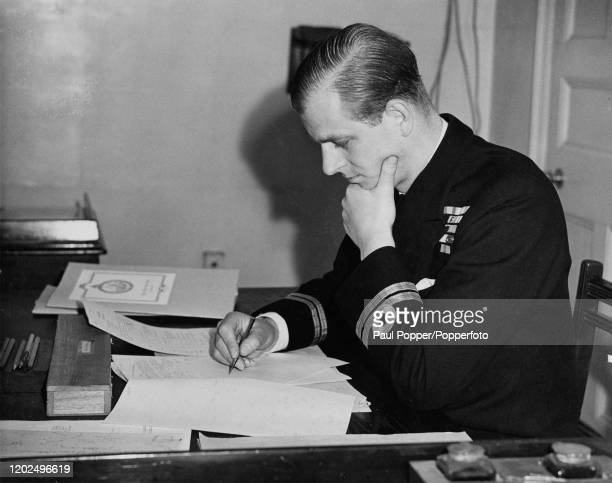Prince Philip Duke of Edinburgh dressed in naval uniform studies papers in the section room when taking a course at the Royal Naval College in...