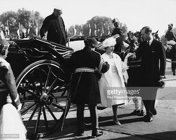 Prince Philip Duke of Edinburgh helps Queen Elizabeth II from a carriage with President Rajendra Prasad of India behind as they attend a Republic Day...