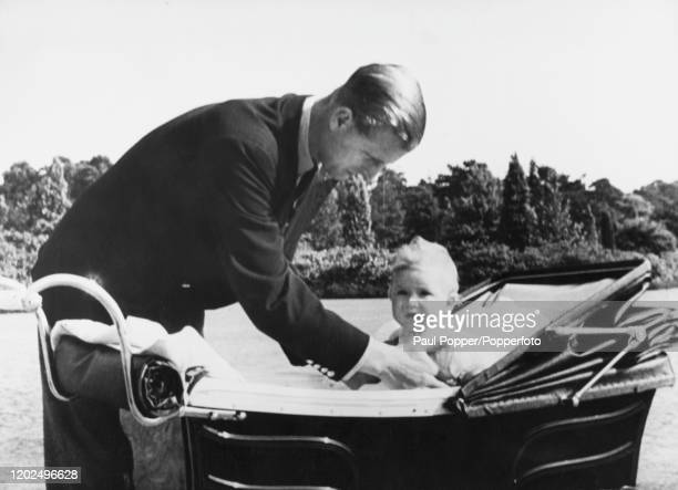 Prince Philip, Duke of Edinburgh holds Prince Charles in his pram during a walk with his son in July 1949.