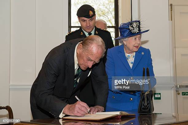 Prince Philip Duke of Edinburgh in his role as ColonelinChief of The Royal Hamilton Light Infantry signs the visitors' book next to Queen Elizabeth...