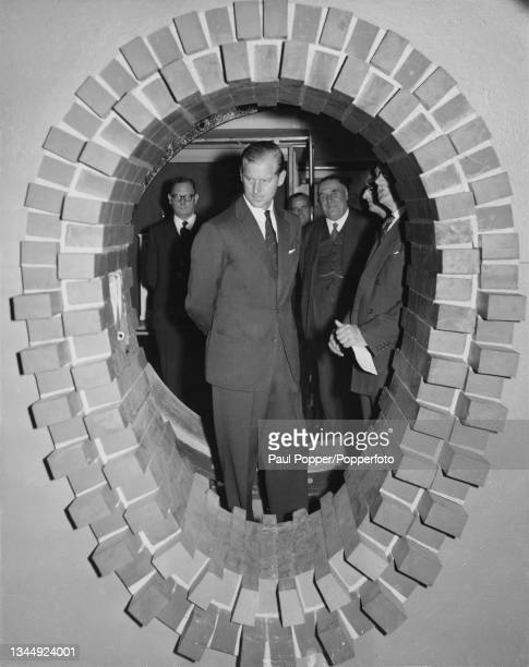 Prince Philip, Duke of Edinburgh inspects a section of sewer pipe at a exhibition to commemorate the centenary of London's main drainage system at...