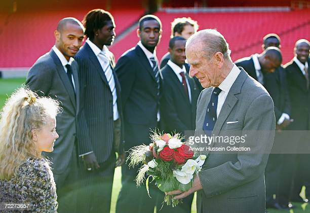 Prince Philip Duke of Edinburgh is presented with a bouquet of flowers by Leah Wenger daughter of Arsenal manager Arsene Wenger as he officially...