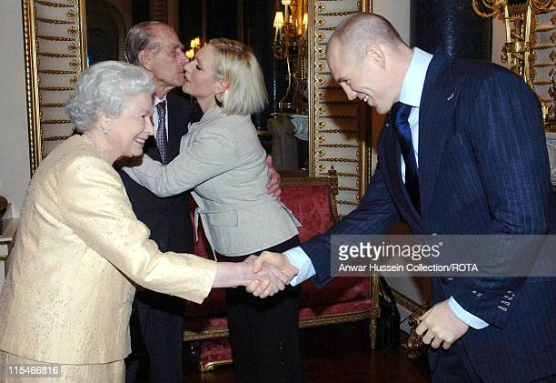 Prince Philip Duke of Edinburgh kisses his granddaughter Zara Phillips as boyfriend English rugby player Mike Tindall shakes hands with Queen...