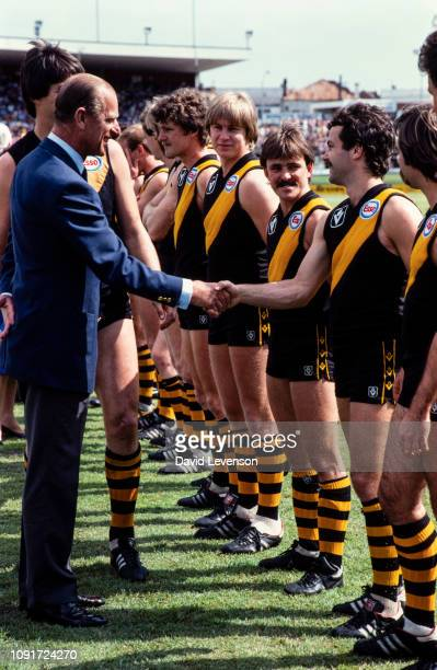 Prince Philip, Duke of Edinburgh, meets the teams at an Aussie Rules exhibition game between Carlton and Richmond on October 6 in Brisbane, Australia