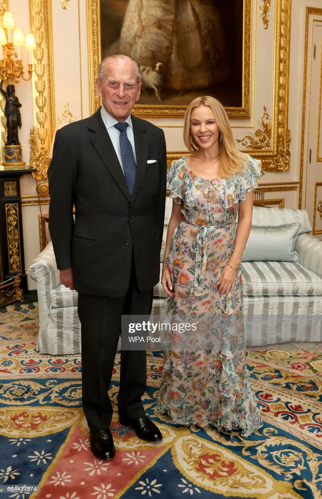 Prince Philip, Duke of Edinburgh, Patron of the Britain-Australia Society, presents Kylie Minogue with the Britain-Australia Society Award for 2016 during a private audience in the White Drawing Room at Windsor Castle on April 4, 2017 in Windsor, United Kingdom.. The Britain-Australia Award recognises Australian and British individuals who have made a significant contribution to the Australia-UK bilateral relationship. Past recipients include Barry Humphries, and the Rt Hon Lord Hague PC.