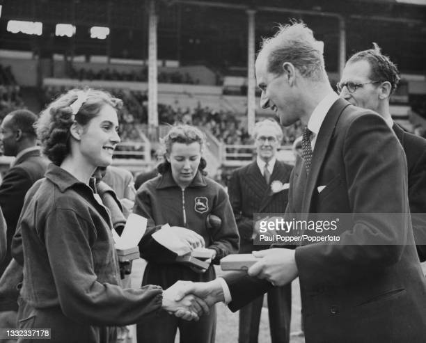 Prince Philip, Duke of Edinburgh presents English sprinter Dorothy Manley with her medal after the Great Britain women's team won the 440 yards relay...