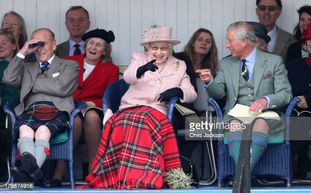 Prince Philip Duke of Edinburgh Queen Elizabeth II and Prince Charles Prince of Wales laugh as they watch the sack race at the annual Braemer...