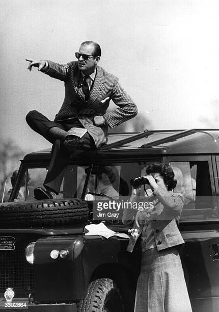 Prince Philip, Duke of Edinburgh seated on the roof of a Land Rover pointing out competitors at the Badminton Horse Trials to Queen Elizabeth II who...