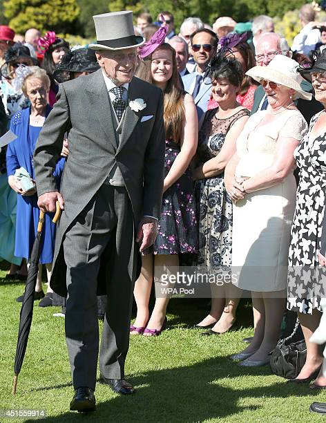 Prince Philip Duke of Edinburgh speaks to guests at a garden party at the Palace of Holyroodhouse on July 1 2014 in Edinburgh Scotland