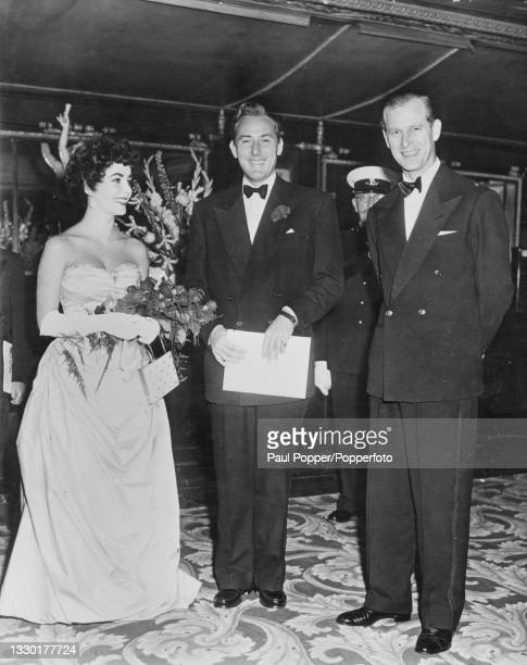 Prince Philip, Duke of Edinburgh stands on right with actress Elizabeth Taylor and her husband, actor Michael Wilding at the premiere of the film...