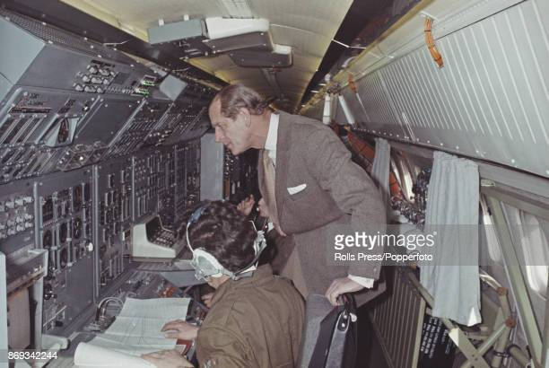 Prince Philip Duke of Edinburgh talks with flight test observer John Allan during a flight in the British assembled prototype Concorde 002 over the...