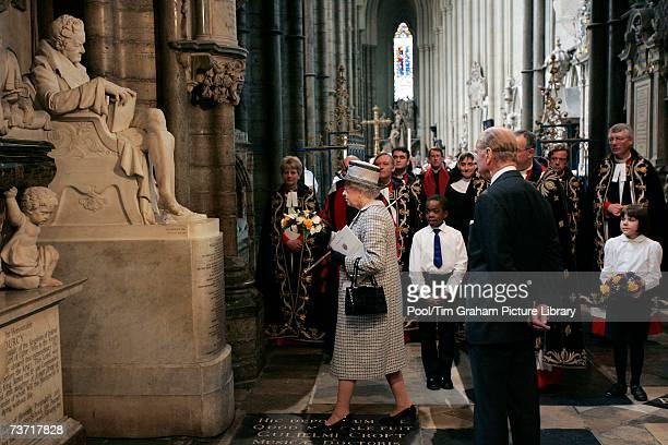 Prince Philip Duke of Edinburgh watches as Queen Elizabeth II lays a wreath on a statue of William Wilberforce in Westminster Abbey during a service...