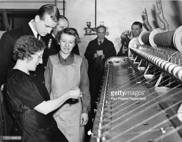 Prince Philip, Duke of Edinburgh watches as two female spinners demonstrate the tying of threads on a loom during a visit to Leafield Woollen Mill in...