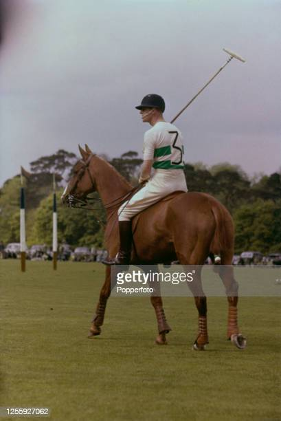 Prince Philip, Duke of Edinburgh, wearing sunglasses on horseback, plays in a polo match in England, June 1957.