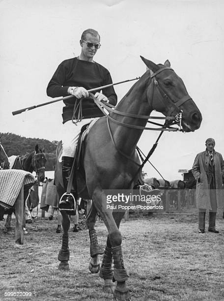 Prince Philip, Duke of Edinburgh, wearing sunglasses on horseback, prepares to commence a game of polo at Windsor Great Park, England, June 10th 1957.