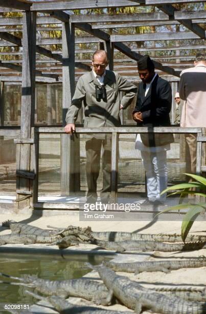 Prince Philip Looking At Alligators At Chitwan Park He Has A Pair Of Binoculars Around His Neck