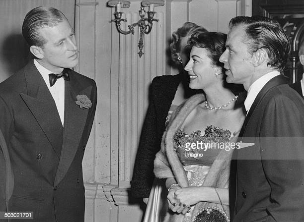 Prince Philip the Duke of Edinburgh is chatting with the USAmerican singer Frank Sinatra and his wife the actress Ava Gardner at London's Empress...