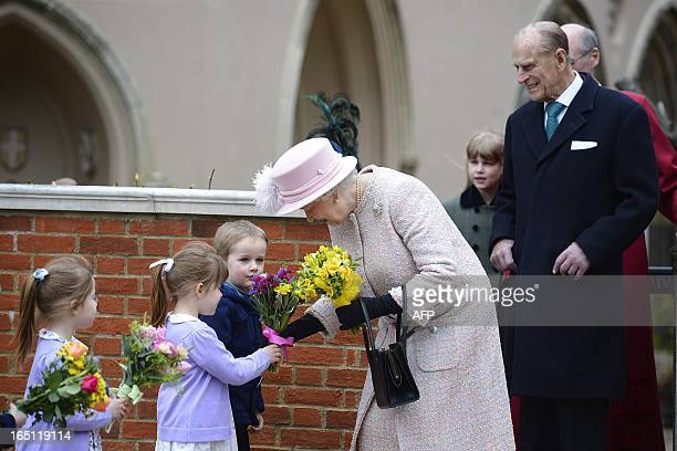 Prince Philip The Duke of Edinburgh looks on a Britain's Queen Elizabeth II receives flowers from children as she leaves The Deanery at St Georges...