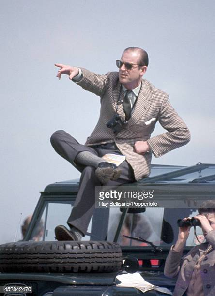 Prince Philip the Duke of Edinburgh pointing atop of a Land Rover whilst his wife Queen Elizabeth II looks through binoculars during the Badminton...