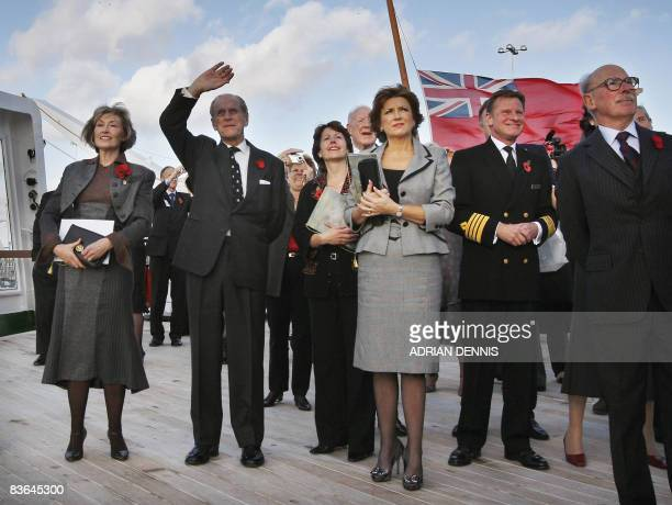 Prince Philip The Duke of Edinburgh shields his eyes from the sun while watching a Harrier jet fly past the ship 'Queen Elizabeth 2' beside Rosie...