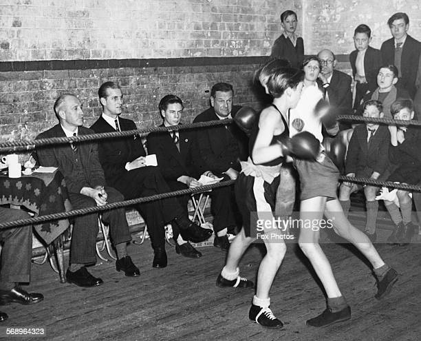 Prince Philip , the Duke of Edinburgh, watching two boys boxing during a visit to the Canterbury Club in Kent, December 10th 1948.