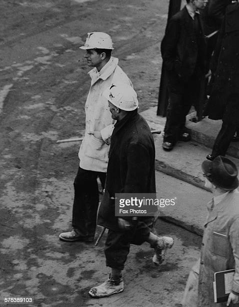 Prince Philip the Duke of Edinburgh wearing a hard hat as he walks with pit manager H Aspinall after a visit underground at Mosley Common Colliery...