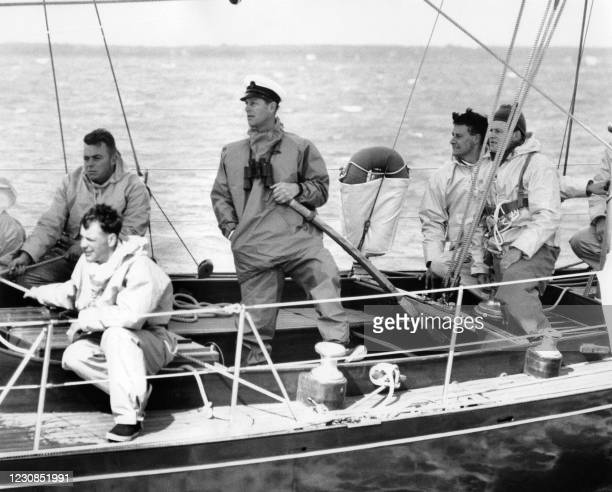 """Prince Philip with binoculars round his neck seen at the helm of the """"Bloodhound"""" on August 7, 1962 during the Britannia challenge cup at Cowes, Isle..."""