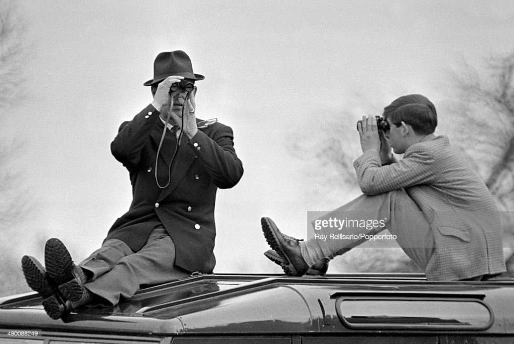 Prince Philip (left) with Prince Charles sitting atop a car and looking in opposite directions through binoculars during the Badminton Horse Trials in Gloucestershire on 9th April 1965.