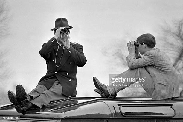 Prince Philip with Prince Charles sitting atop a car and looking in opposite directions through binoculars during the Badminton Horse Trials in...