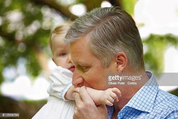 Prince Philippe kisses his daughter Princess Eleonore on the arm in the garden of the royal castle of Laeken