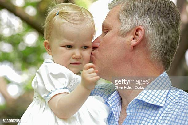 Prince Philippe kisses his daughter Princess Eleonore on the cheek in the garden of the royal castle of Laeken