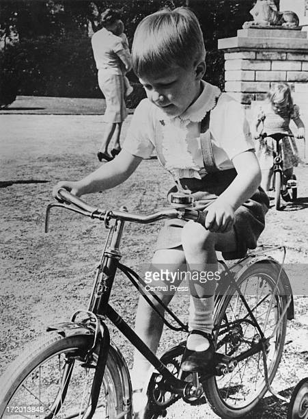Prince Philippe of Belgium enjoys a ride on his bicycle in the grounds of the Chateau Belvedere on the day before his 5th birthday 14th April 1965...
