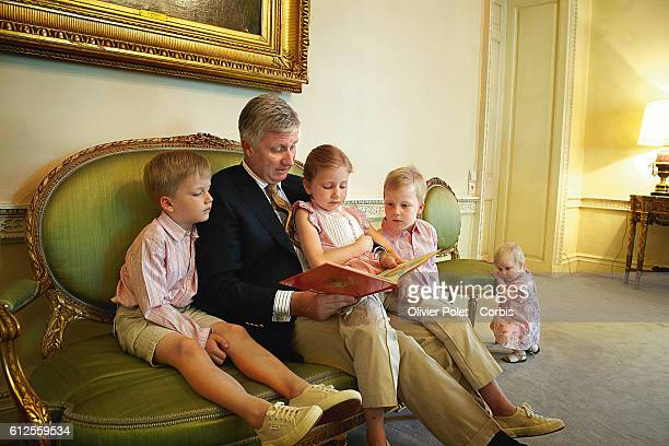 Prince Philippe of Belgium reads a book to his children : Gabriel, Elisabeth, Emmanuel, and Eleonore, in the music room of the royal castle of Laeken.