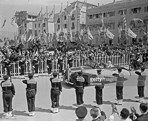 Prince Rainier and Princess Grace are driven to the royal palace past cheering crowds after the religious ceremony in the Cathedral of St. Nicholas...