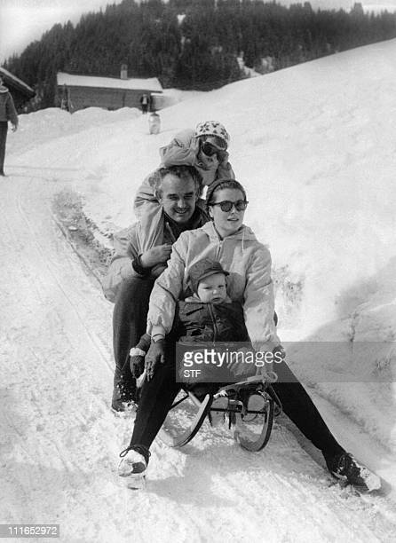 Prince Rainier and Princess Grace of Monaco and children Caroline and Albert slide down a road in Switzerland during winter vacations 26 February 1960