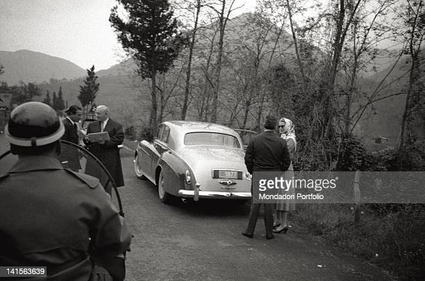 Prince Rainier Grimaldi of Monaco is talking with his wife Grace Kelly, next to their Rolls-Royce, while they are travelling to Rome. The prince is...