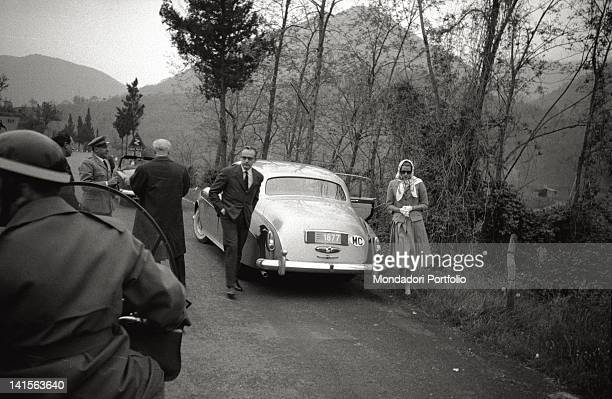 Prince Rainier Grimaldi of Monaco with his wife Grace Kelly are travelling to Rome They have just got off their RollsRoyce The prince is now going to...