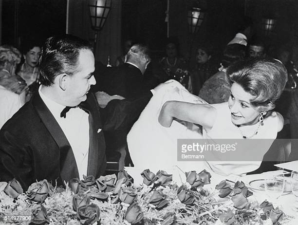 Prince Rainier III of Monaco gives a helping hand to Mrs Tina Onassis the beautiful wife of Greek shipping magnate Aristotle Onassis during the gala...