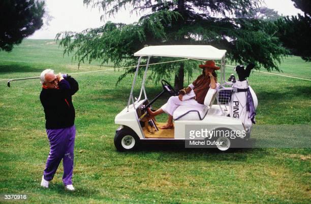 Prince Rainier III of Monaco plays a shot with Princess Caroline in the cab at Monaco golf de Montagel in 1983 in Monte Carlo Monaco