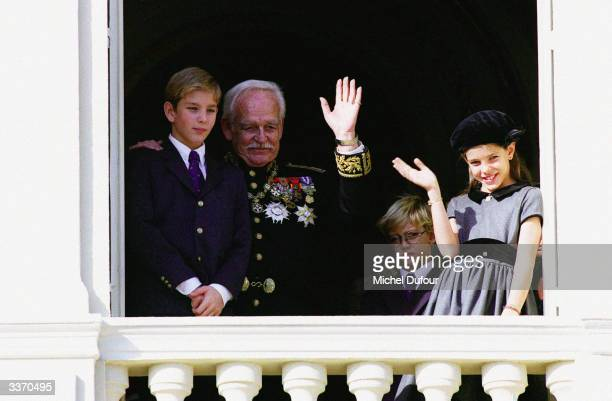 Prince Rainier III of Monaco waves from the balcony of the palace with Prince Albert and Prince Andrea celebrating principality's National Day on...