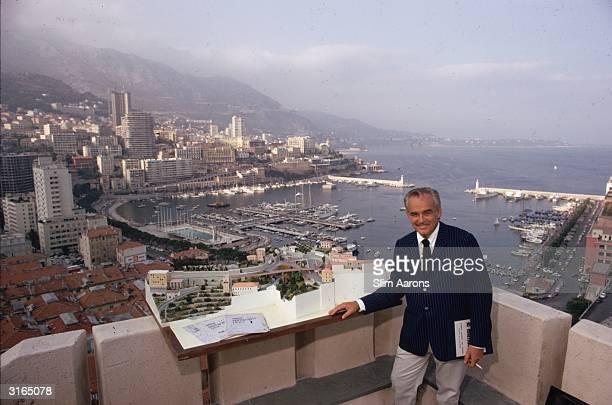 Prince Rainier III stands on a terrace overlooking Monaco and its harbour with an architect's model of the city balanced on the parapet beside him