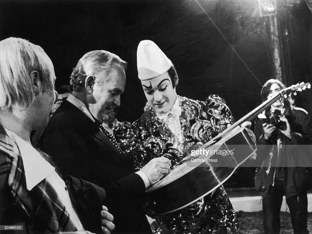 Prince Rainier of Monaco pays a visit to the Knie Circus in Vevey, 15th October 1974. After the show, he signs his autograph on a guitar belonging to the clown Rivel.