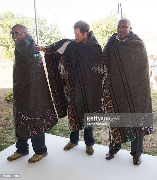 Prince Seeiso of Lesotho, Prince Harry and King Letsie III of Lesotho wear shawls given to them as a gift as they attend the opening of Sentebale's...