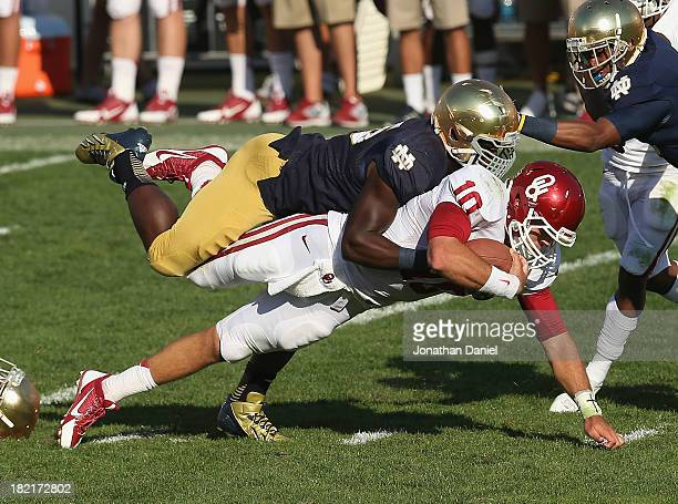 Prince Shembo of the Notre Dame Fighting Irish brings down Blake Bell of the Oklahoma Sooners at Notre Dame Stadium on September 28 2013 in South...