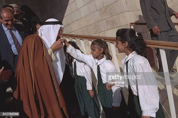 Prince Talal kissing a girl's hand