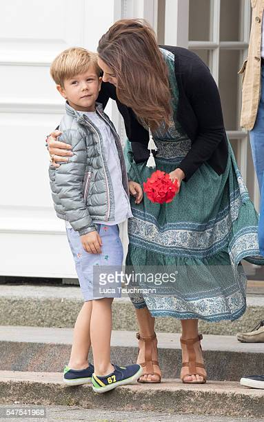 Prince Vincent of Denmark is embraced by his mother Crown Princess Mary of Denmark during the annual summer photo call for The Danish Royal Family at...
