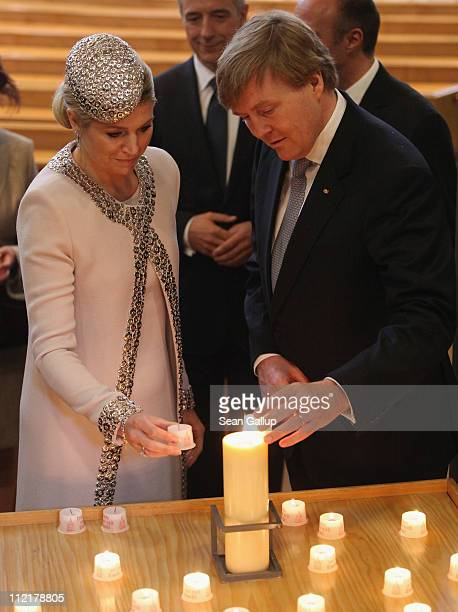 Prince WillemAlexander and Princess Maxima of the Netherlands light a candle at the Frauenkirche Cathedral on April 14 2011 in Dresden Germany The...