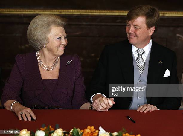Prince WillemAlexander of the Netherlands holds hands with his mother Queen Beatrix of the Netherlands during her abdication ceremony in the...